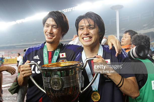 Daisuke Suzuki and Yuhei Tokunaga of Japan celebrate with the trophy after winning the EAFF East Asian Cup 2013 against South Korea at Jamsil Stadium...