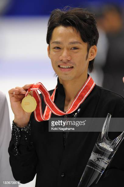 Daisuke Takahashi of Japan with a gold medal poses for photograghs in the men's singles during day three of the ISU Grand Prix of Figure Skating NHK...