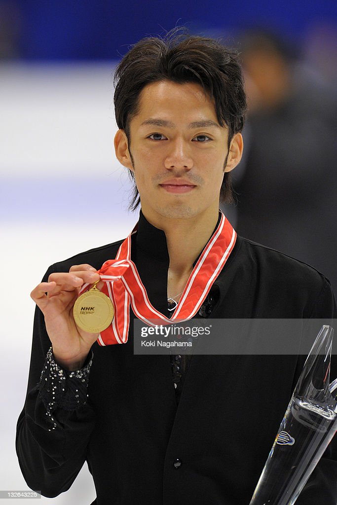 Daisuke Takahashi of Japan with a gold medal poses for photographs in the men's singles during day three of the ISU Grand Prix of Figure Skating NHK...