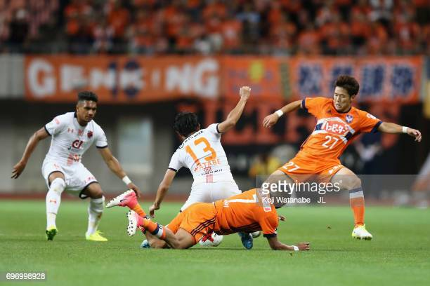 Daisuke Watabe of Omiya Ardija is challenged by Rony and Yuto Horigome of Albirex Niigata during the JLeague J1 match between Albirex Niigata and...