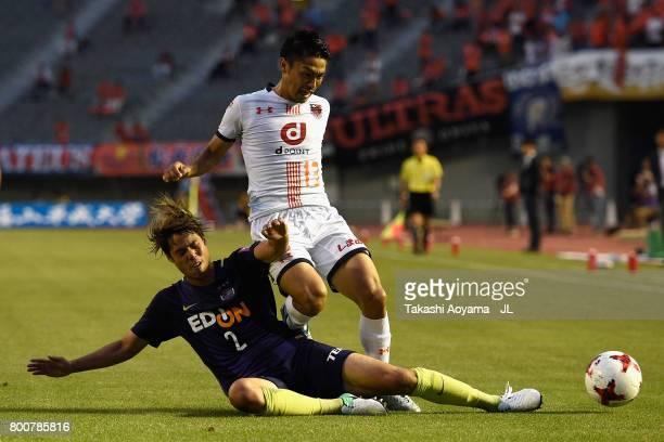 Daisuke Watabe of Omiya Ardija is tackled by Yuki Nogami of Sanfrecce Hiroshima during the JLeague J1 match between Sanfrecce Hiroshima and Omiya...