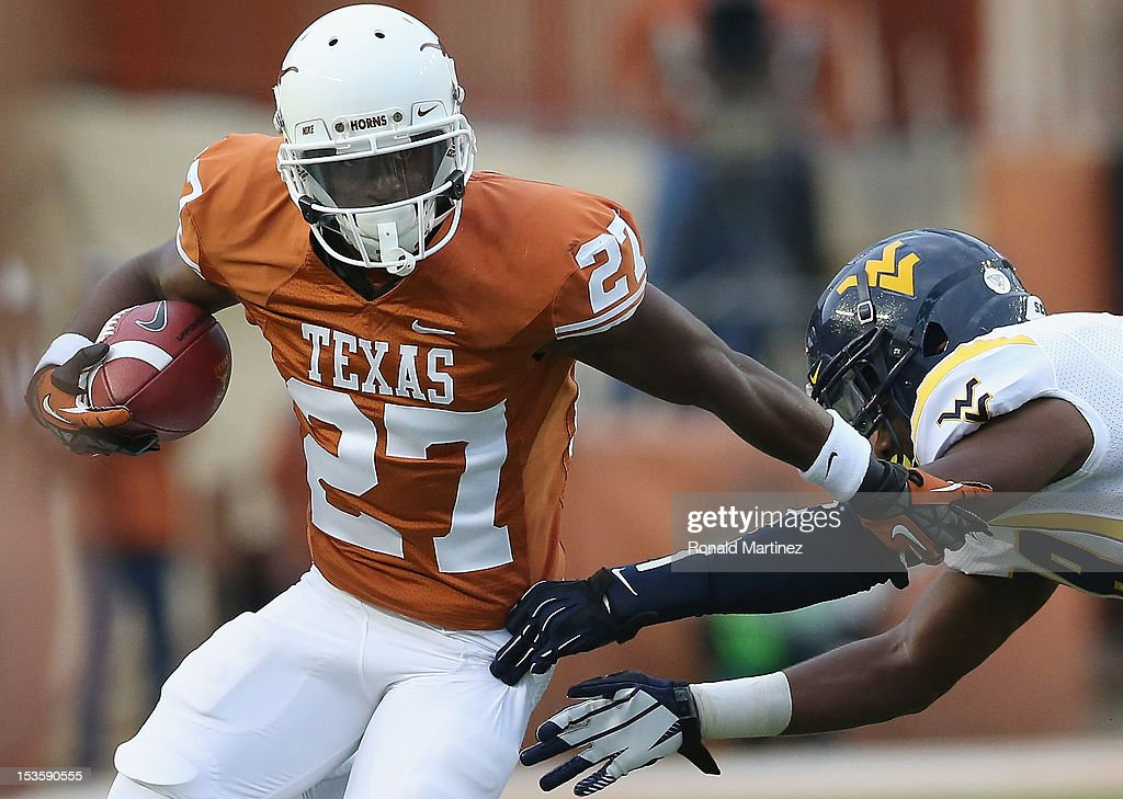 Daje Johnson #27 of the Texas Longhorns runs the ball against Terence Garvin #28 of the West Virginia Mountaineers at Darrell K Royal-Texas Memorial Stadium on October 6, 2012 in Austin, Texas.