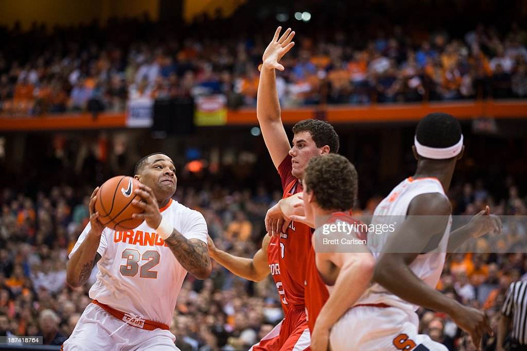 Dajuan Coleman #32 of Syracuse Orange is fouled while going up for a shot in a basketball game against Cornell Big Red on November 8, 2013 at the Carrier Dome in Syracuse, New York.
