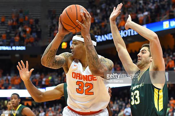 DaJuan Coleman of the Syracuse Orange controls the ball against the defense of Connor Mahoney of Le Moyne Dolphins during the first half at the...