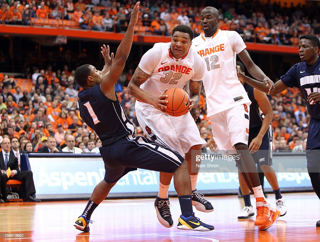 DaJuan Coleman #32 of the Syracuse Orange drives to the basket against Dion Nesmith #1 of the Monmouth Hawks during the game at the Carrier Dome on December 8, 2012 in Syracuse, New York.