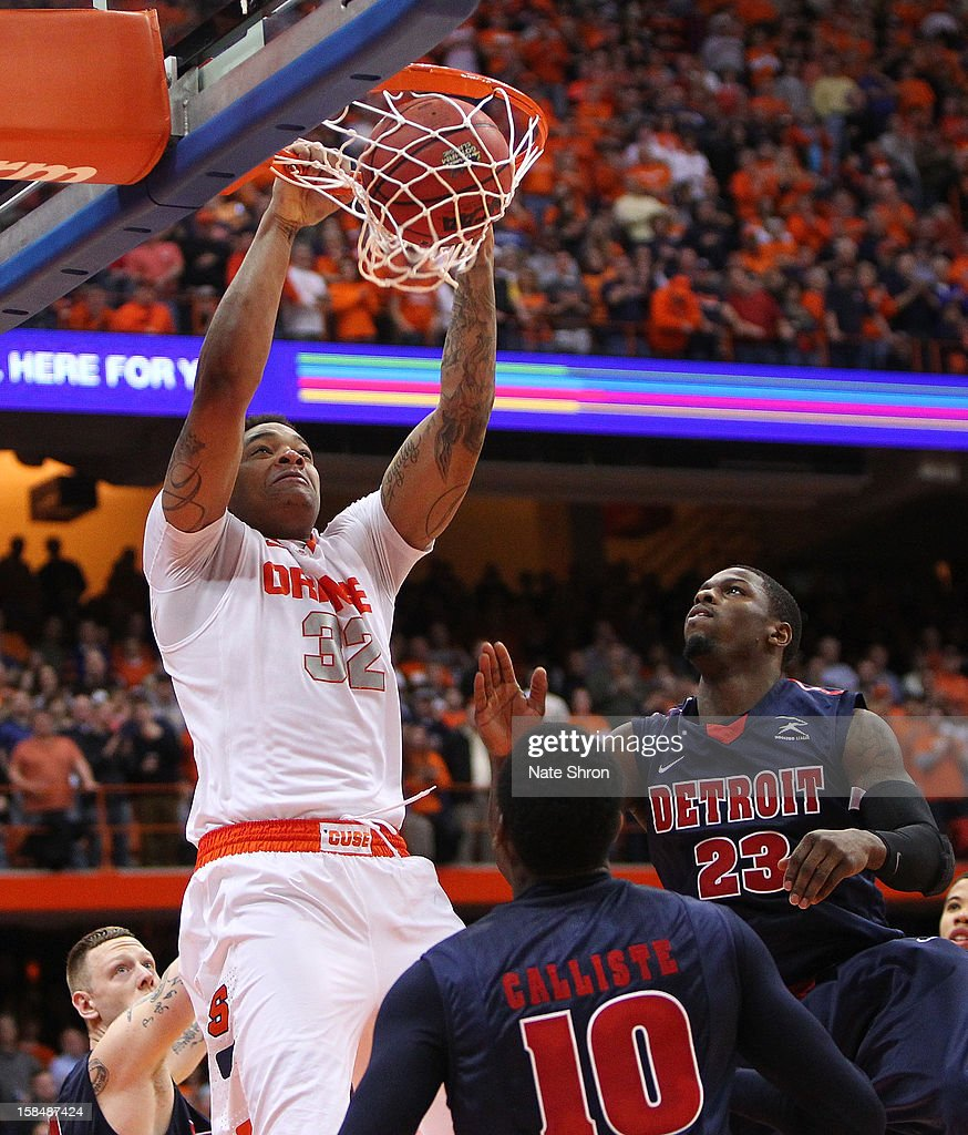 DaJuan Coleman #32 of the Syracuse Orange dunks the ball against Doug Anderson #23, Jason Calliste #10 and Nick Minnerath #34 of the Detroit Titans during the game at the Carrier Dome on December 17, 2012 in Syracuse, New York.