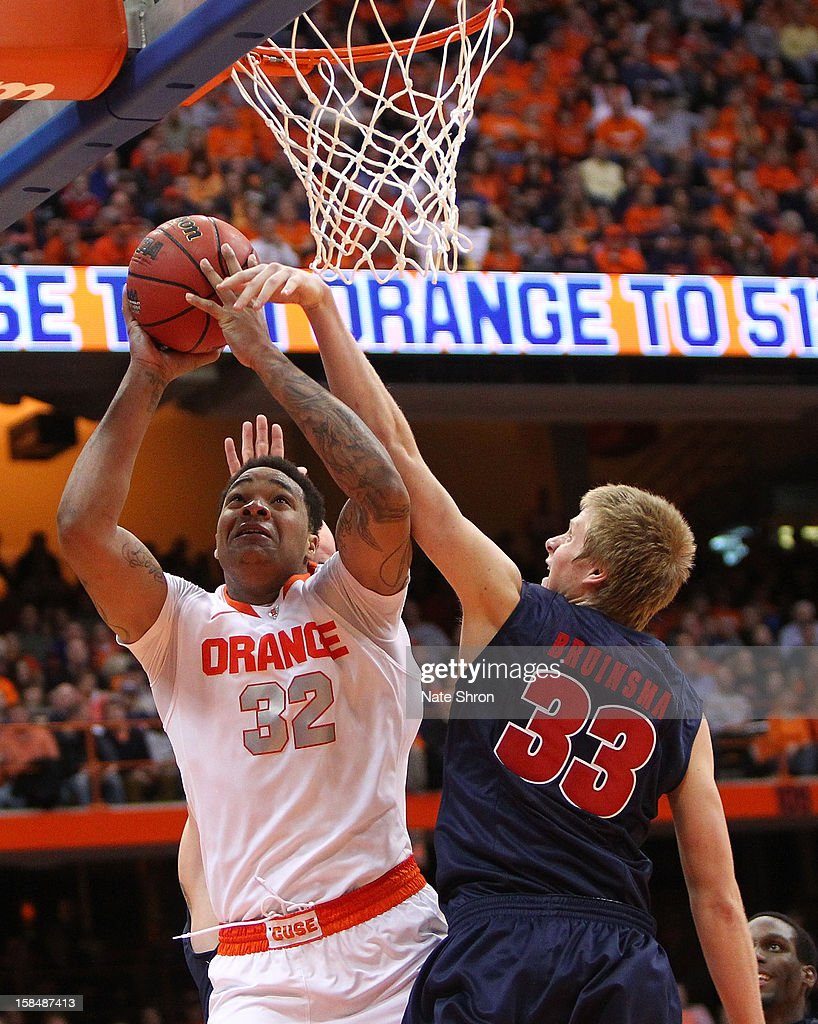DaJuan Coleman #32 of the Syracuse Orange puts the ball up to the basket against Evan Bruinsma #33 of the Detroit Titans during the game at the Carrier Dome on December 17, 2012 in Syracuse, New York.