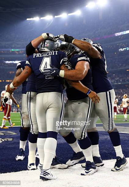 Dak Prescott of the Dallas Cowboys celebrates with teammates after scoring a touchdown during the fourth quarter against the Washington Redskins at...