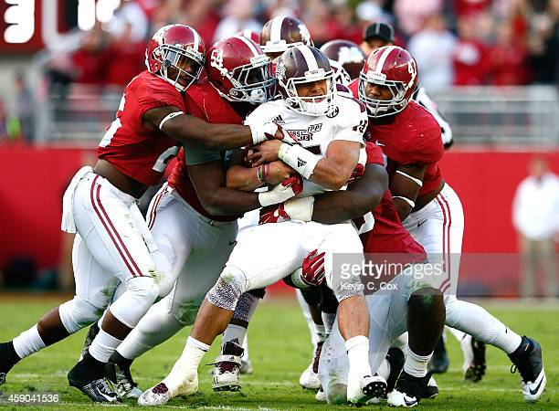 Dak Prescott of the Mississippi State Bulldogs is tackled by Landon Collins Dalvin Tomlinson and Xzavier Dickson of the Alabama Crimson Tide at...
