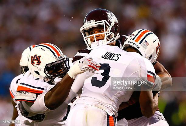 Dak Prescott of the Mississippi State Bulldogs rushes for a first down in the final minutes against Montravius Adams and Jonathan Jones of the Auburn...