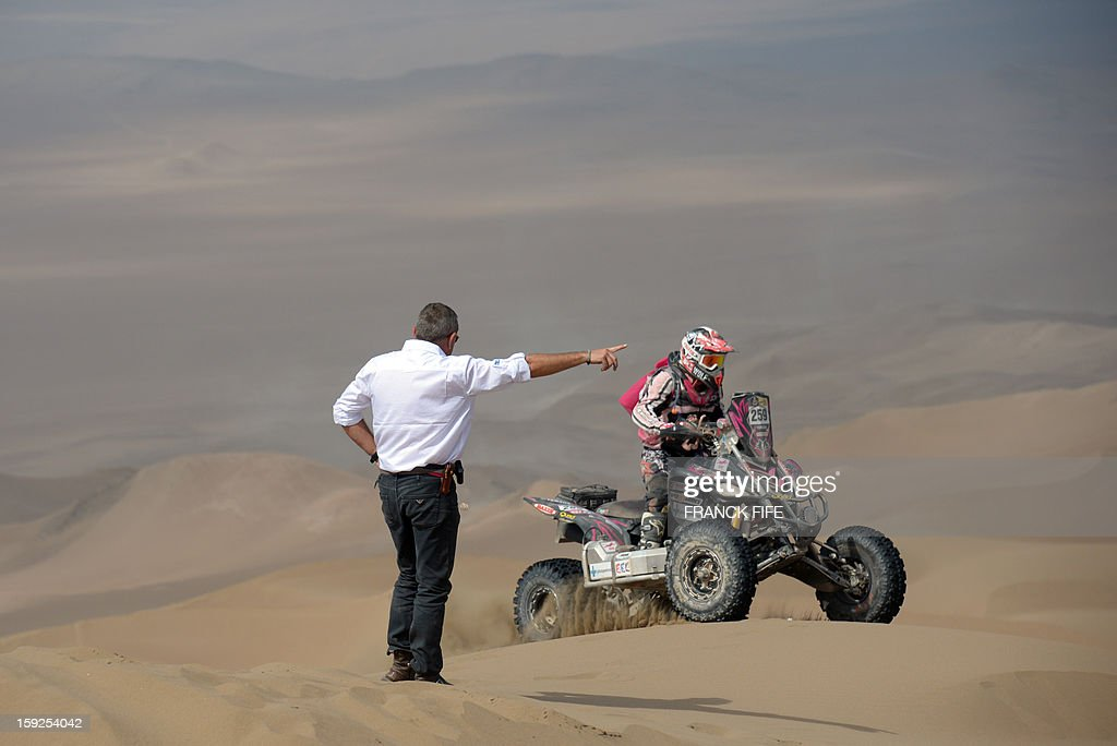 Dakar Rally director Etienne Lavigne indicates the way to Italian quad driver Camelia Liparoti during the Stage 6 of the 2013 Dakar Rally between Arica and Calama, Chile, on January 10, 2013. The rally is taking place in Peru, Argentina and Chile from January 5 to 20.