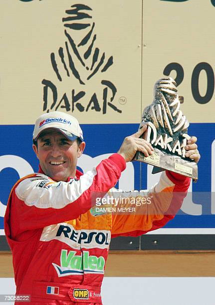 Frenchman Stephane Peterhansel celebrates with his trophy on the podium after winning the 29th Dakar 21 January 2007 It was Peterhansel's third Dakar...