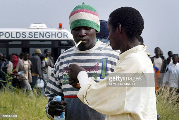 Senegalese wouldbe immigrants light cigarettes as they are transferred from buses to a hangar beside the Leopold Sedar Senghor airport outside Dakar...