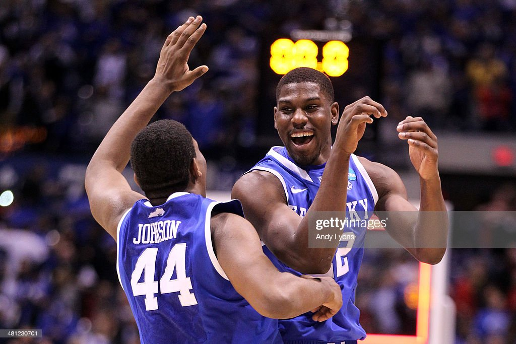 Dakari Johnson #44 and Alex Poythress #22 of the Kentucky Wildcats celebrate defeating the Louisville Cardinals 74 to 69 during the regional semifinal of the 2014 NCAA Men's Basketball Tournament at Lucas Oil Stadium on March 28, 2014 in Indianapolis, Indiana.