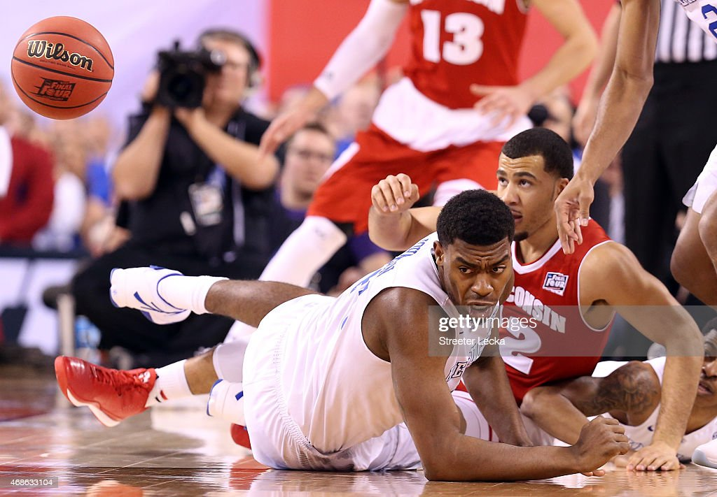Dakari Johnson of the Kentucky Wildcats and Traevon Jackson of the Wisconsin Badgers fall to the court going for a loose ball in the first half...