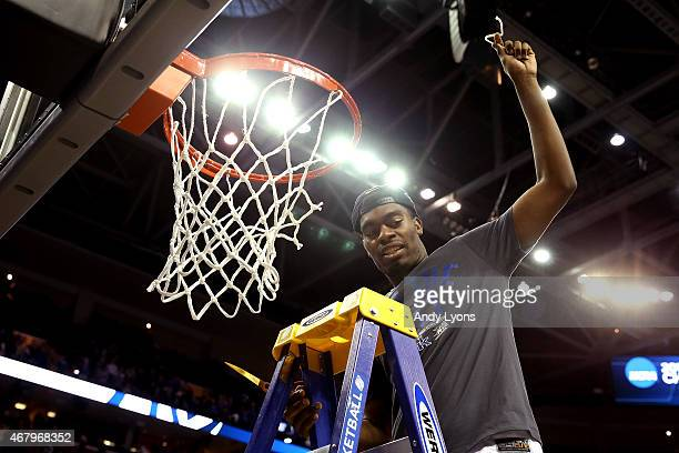 Dakari Johnson of the Kentucky Wildcats cuts down the nets after defeating the Notre Dame Fighting Irish during the Midwest Regional Final of the...