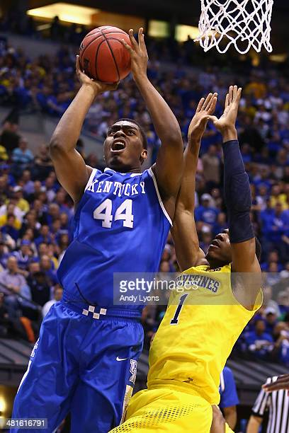 Dakari Johnson of the Kentucky Wildcats shoots the ball over Glenn Robinson III of the Michigan Wolverines during the midwest regional final of the...