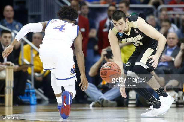 Dakota Mathias of the Purdue Boilermakers and Devonte' Graham of the Kansas Jayhawks chase a loose ball during the 2017 NCAA Men's Basketball...