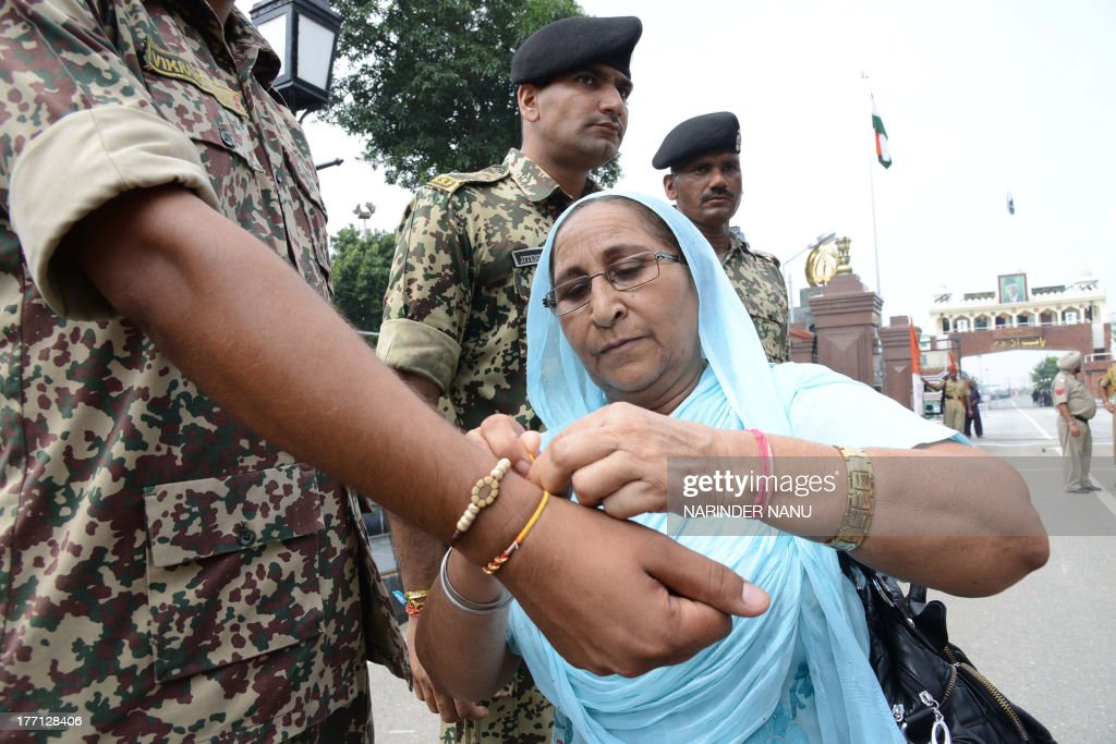 Dalbir Kaur, (C), sister of Sarabjit Singh, an Indian death row prisoner fatally assaulted in Pakistan, ties a sacred thread or rakhi onto the wrist of an Indian Border Security Force (BSF) soldier at the Indo-Pakistan Wagah border post on August 21, 2013. The annual festival of Raksha Bandhan, which commemorates the abiding ties between siblings of opposite sex, is marked by a very simple ceremony in which a woman ties a rakhi, which may be a colorful thread, a simple bracelet, or a decorative string, around the wrist of her brother.