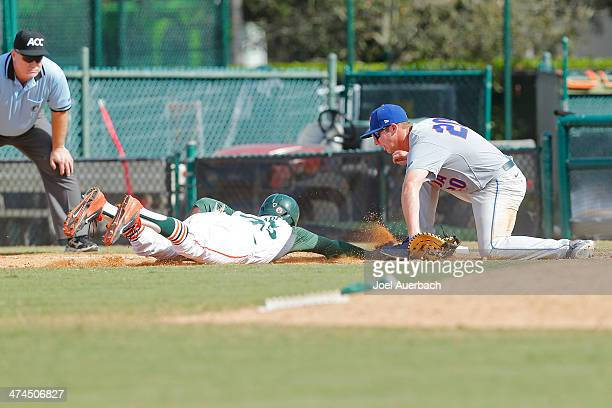Dale Carey of the Miami Hurricanes gets back to first base safe ahead of the tag by Peter Alonso of the Florida Gators on February 23 2014 at Alex...