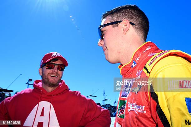 Dale Earnhardt Jr and Alex Bowman driver of the Axalta Chevrolet talk before the NASCAR Sprint Cup Series Bank of America 500 at Charlotte Motor...