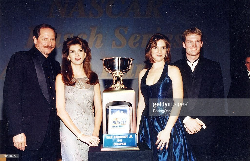 Dale Earnhardt, Jr., and his proud father, Dale, Sr., pose for photos after Junior received the NASCAR Busch Series Championship Cup in New York, New York in December, 1998. Also on stage are his stepmother, Teresa Earnhardt (next to Dale, Sr.) and sister, Kelley.