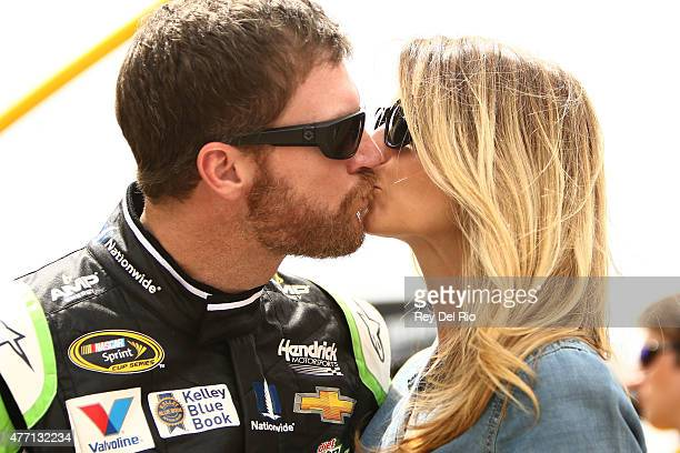 Dale Earnhardt Jr driver of the AMP ENERGY Chevrolet kisses his girlfriend Amy Reimann prior to the NASCAR Sprint Cup Series Quicken Loans 400 at...