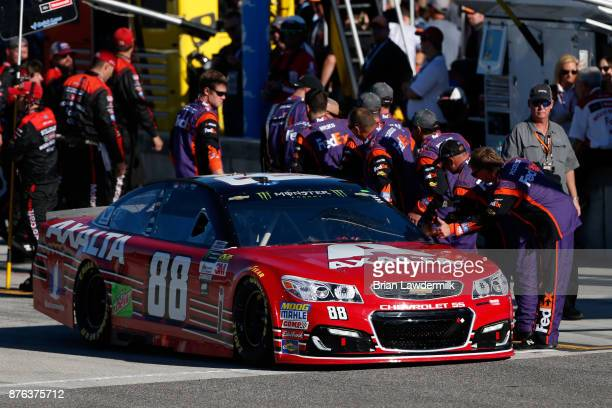 Dale Earnhardt Jr driver of the AXALTA Chevrolet is greeted by crew members of Denny Hamlin driver of the FedEx Express Toyota as he drives on pit...