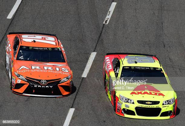 Dale Earnhardt Jr driver of the Axalta Chevrolet leads Daniel Suarez driver of the ARRIS Toyota during the Monster Energy NASCAR Cup Series STP 500...