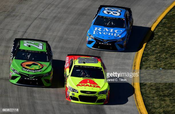 Dale Earnhardt Jr driver of the Axalta Chevrolet leads Gray Gaulding driver of the SunFrogcom Toyota and Corey LaJoie driver of the RMC Events Toyota...