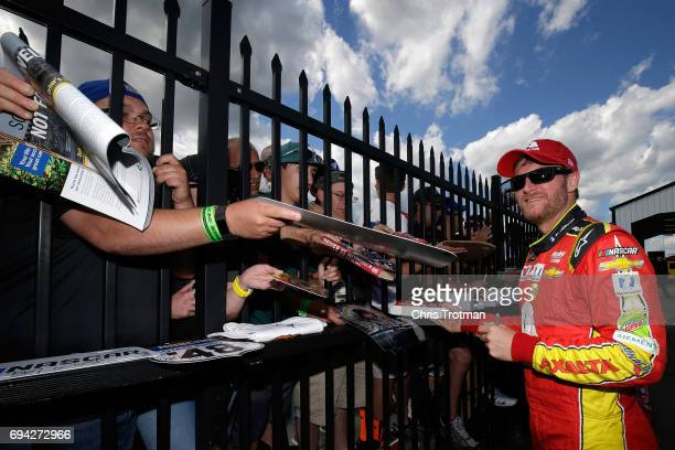 Dale Earnhardt Jr driver of the Axalta Chevrolet signs autographs for fans prior to qualifying for the Monster Energy NASCAR Cup Series Axalta...