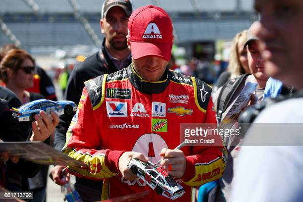 Dale Earnhardt Jr driver of the Axalta Chevrolet signs autographs during practice for the Monster Energy NASCAR Cup Series STP 500 at Martinsville...