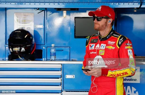 Dale Earnhardt Jr driver of the Axalta Chevrolet stands in the garage areduring practice for the Monster Energy NASCAR Cup Series Camping World 500...