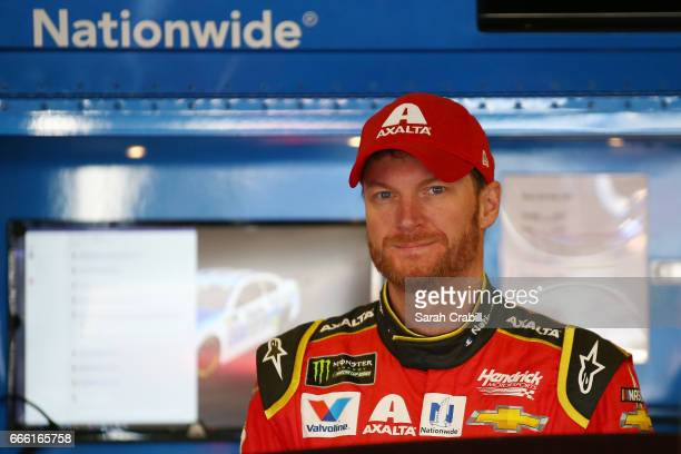 Dale Earnhardt Jr driver of the Axalta Chevrolet stands in the garage area during practice for the Monster Energy NASCAR Cup Series O'Reilly Auto...
