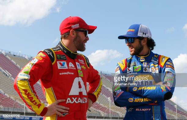 Dale Earnhardt Jr driver of the Axalta Chevrolet talks to Chase Elliott driver of the NAPA Chevrolet on the grid during qualifying for the Monster...