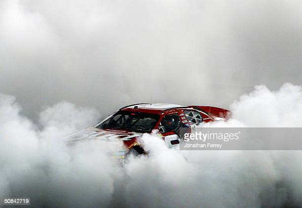 Dale Earnhardt Jr driver of the Budweiser Chevrolet celebrates with a victory burnout winning the NASCAR Nextel Cup Chevy American Revolution 400 on...