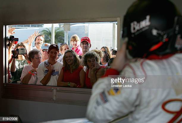 Dale Earnhardt Jr driver of the Budweiser Chevrolet puts on his helmet in the garage as fans watch on during Nascar Nextel Cup testing on January 12...