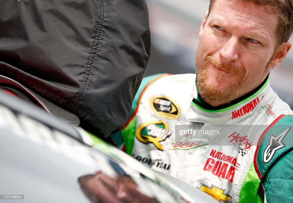 Dale Earnhardt Jr., driver of the #88 Diet Mountain Dew Chevrolet, climbs into his car in the garage area during practice for the NASCAR Sprint Cup Series IRWIN Tools Night Race at Bristol Motor Speedway on August 23, 2013 in Bristol, Tennessee.
