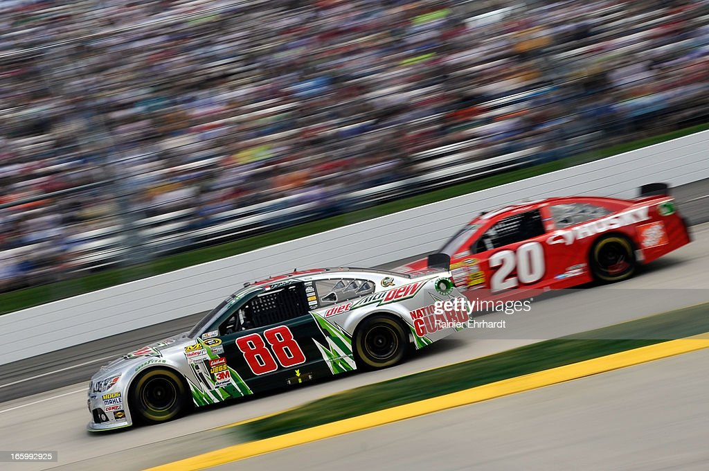 Dale Earnhardt Jr., driver of the #88 Diet Mountain Dew Chevrolet, leads Matt Kenseth, driver of the #20 The Home Depot/Husky Toyota, during the NASCAR Sprint Cup Series STP Gas Booster 500 on April 7, 2013 at Martinsville Speedway in Ridgeway, Virginia.