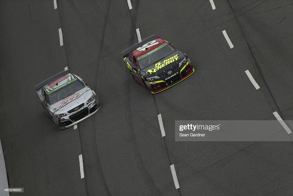 Dale Earnhardt Jr., driver of the #88 Diet Mountain Dew Chevrolet, races with Clint Bowyer, driver of the #15 5-hour ENERGY Toyota, during the NASCAR Sprint Cup Series STP 500 at Martinsville Speedway on March 30, 2014 in Martinsville, Virginia.