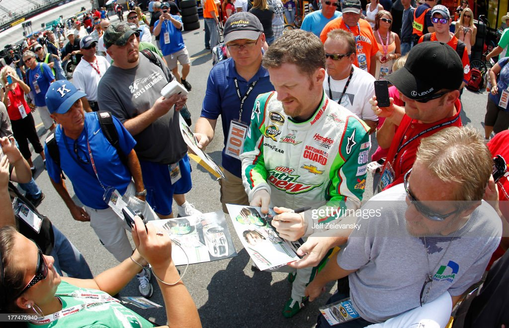 Dale Earnhardt Jr., driver of the #88 Diet Mountain Dew Chevrolet, sign autographs for fans in the garage area during practice for the NASCAR Sprint Cup Series IRWIN Tools Night Race at Bristol Motor Speedway on August 23, 2013 in Bristol, Tennessee.