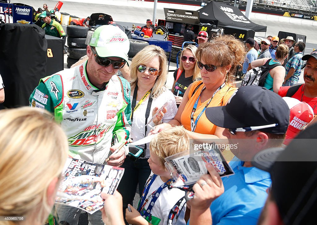 Dale Earnhardt Jr., driver of the #88 Diet Mountain Dew Chevrolet, signs autographs during practice for the NASCAR Sprint Cup Series Irwin Tools Night Race at Bristol Motor Speedway on August 22, 2014 in Bristol, Tennessee.