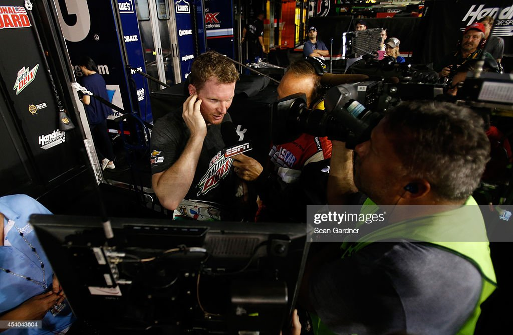 Dale Earnhardt Jr., driver of the #88 Diet Mountain Dew Chevrolet, speaks to the media following an incident during the NASCAR Sprint Cup Series Irwin Tools Night Race at Bristol Motor Speedway on August 23, 2014 in Bristol, Tennessee.