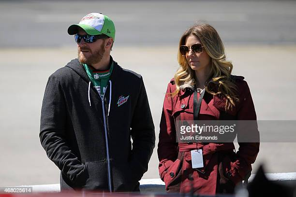 Dale Earnhardt Jr driver of the Diet Mountain Dew Chevrolet stands on the grid with his girlfriend Amy Reimann prior to the NASCAR Sprint Cup Series...