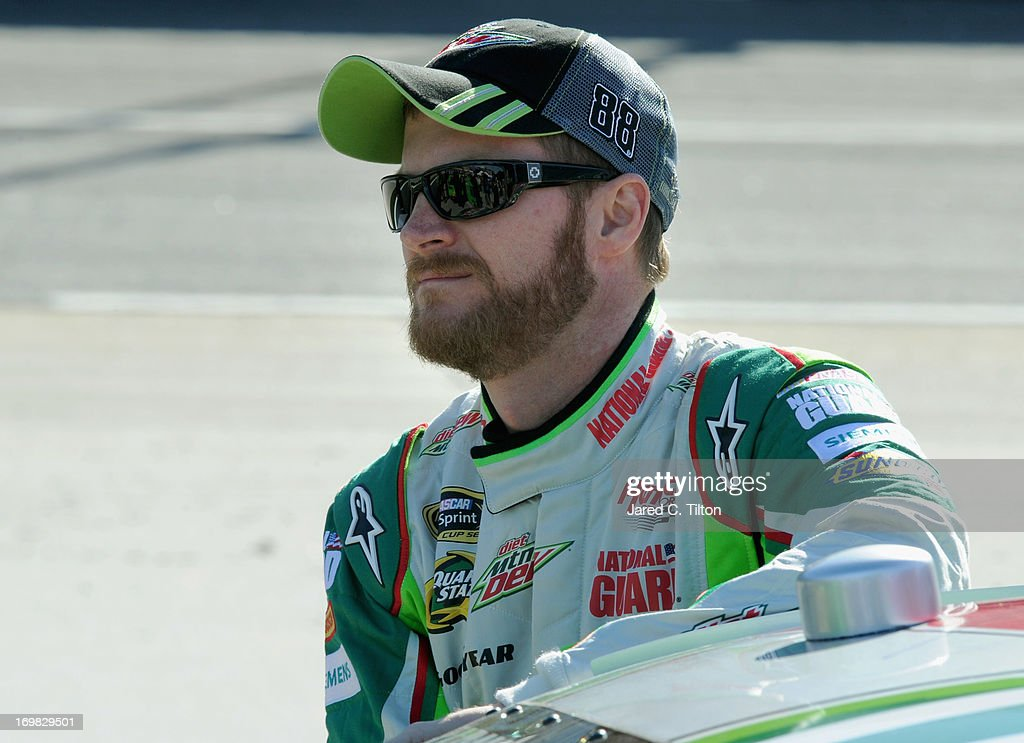 Dale Earnhardt Jr., driver of the #88 Diet Mountain Dew Chevrolet, waits by his car during qualifying for the NASCAR Sprint Cup Series STP Gas Booster 500 on April 5, 2013 at Martinsville Speedway in Ridgeway, Virginia.