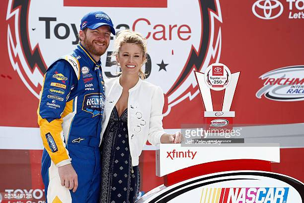 Dale Earnhardt Jr driver of the Hellmann's Chevrolet poses for a photo with his girlfriend Amy Reimann in Victory Lane after winning the NASCAR...