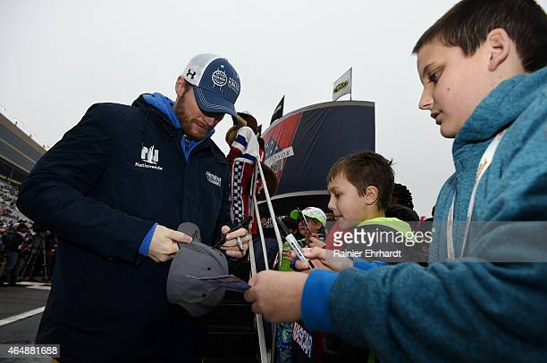 Dale Earnhardt Jr driver of the Kelley Blue Book Chevrolet signs autographs for fans before the NASCAR Sprint Cup Series Folds of Honor QuikTrip 500...