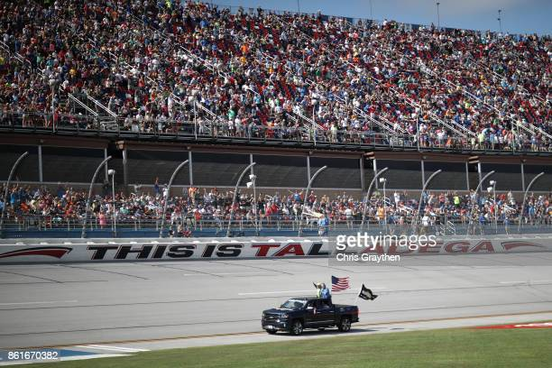 Dale Earnhardt Jr driver of the Mountain Dew Chevrolet waves to the crowd on his driver introduction lap prior to the Monster Energy NASCAR Cup...