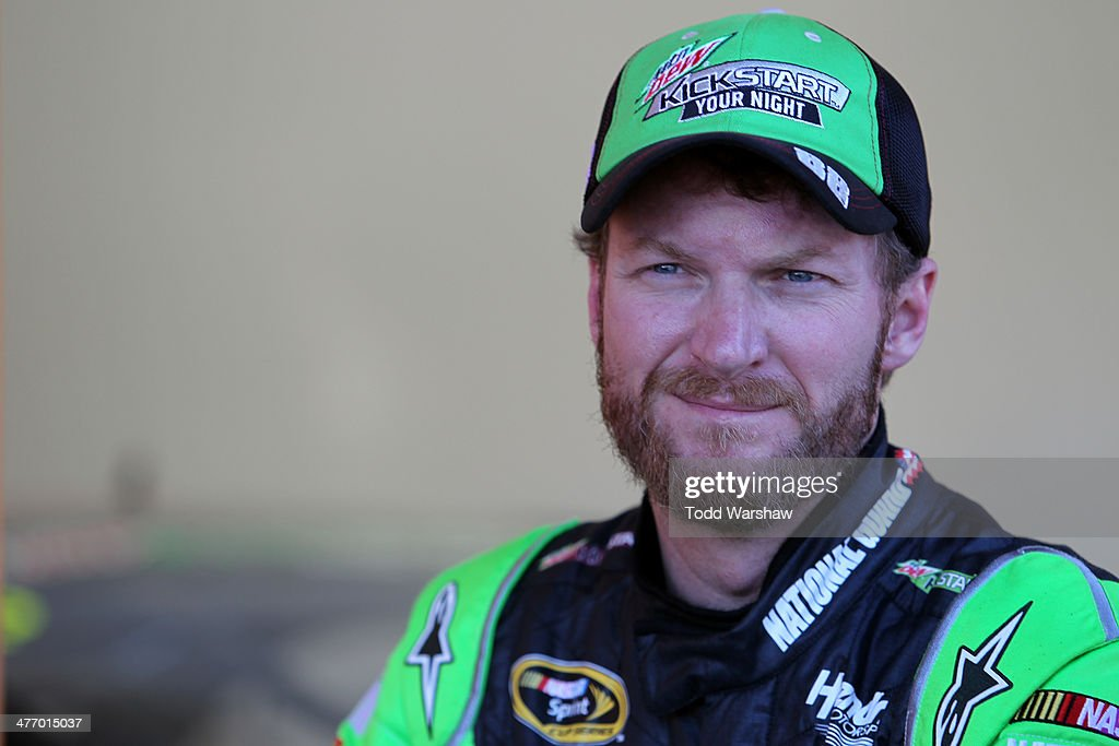 Dale Earnhardt Jr., driver of the #88 Mountain Dew Kickstart Chevrolet, stands in the garage during a testing session at Las Vegas Motor Speedway on March 6, 2014 in Las Vegas, Nevada.