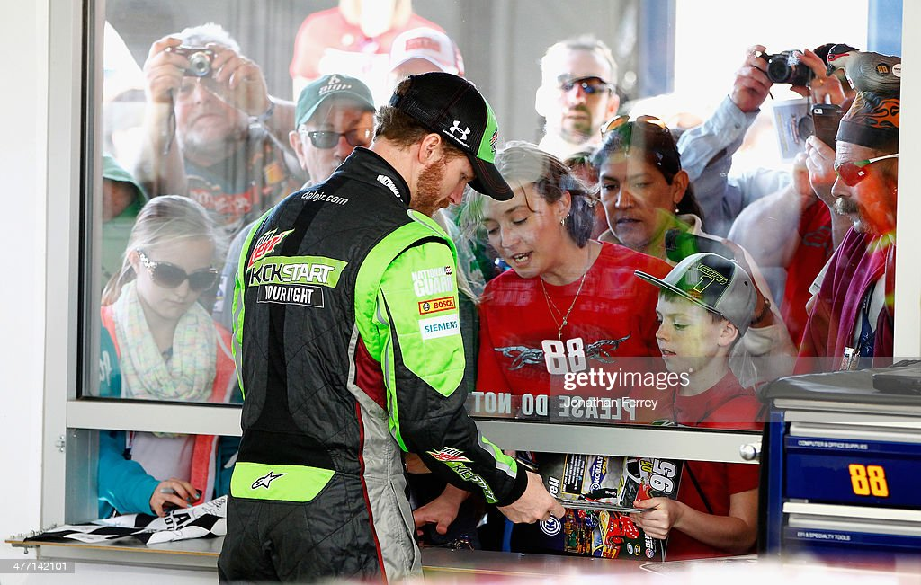 Dale Earnhardt Jr., driver of the #88 Mountain Dew Kickstart Chevrolet, signs autographs in the garage area during practice for the NASCAR Sprint Cup Series Kobalt 400 at Las Vegas Motor Speedway on March 7, 2014 in Las Vegas, Nevada.